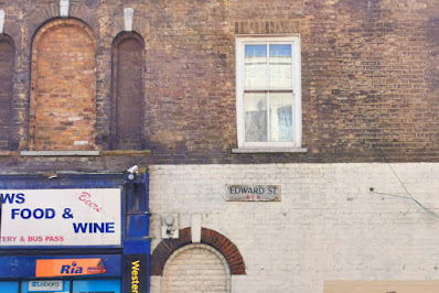 Photograph of part of a Victorian brick wall with a sign reading 'EDWARD STREET S.E.8' in the centre. The metal sign is rusted and damaged at the edges; the writing is in black on dirty white, with the postcode in red. Above it is a window. Below is the top of a bricked-up arched window. To the left are three arched windows, now bricked up, and part of a white sign with blue text, for a food and wine shop.