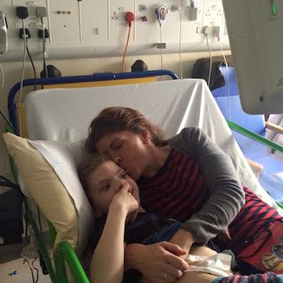 Photo of Daisy in a hospital bed with Steph in bed cuddling her