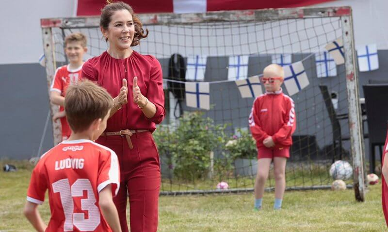 Crown Princess Mary wore a banora red gathered silk blouse from Hugo Boss, and ivory white cashmere coat from Boss. Denmark and Finland
