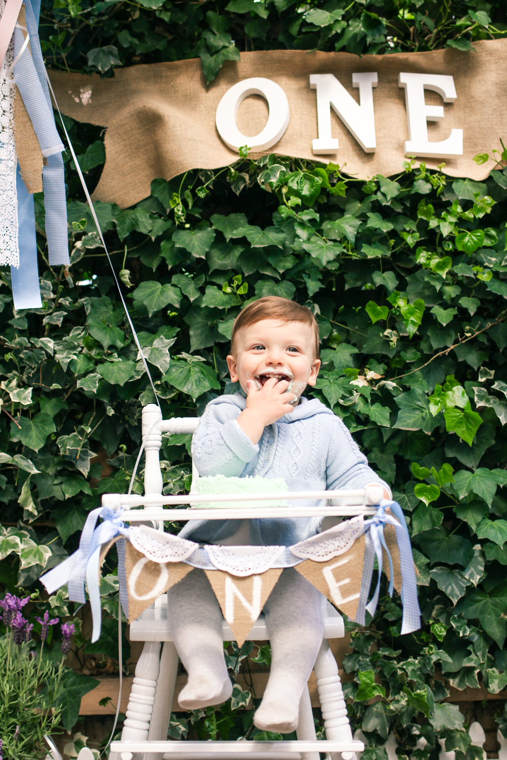 Baby cake smash in vintage  high chair and bunting for babys Peter Rabbit themed first birthday