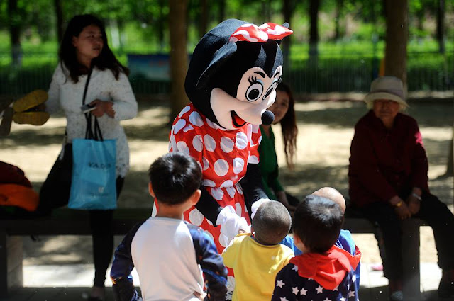 Old woman wears Mickey Mouse costume to pay relative's medical bills