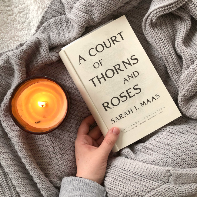 Title page of 'A Court of Thorns and Roses' on a grey cardigan next to a lit candle