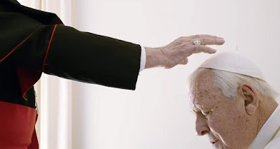 "Movie still for Netflix's original film ""The Two Popes"" featuring Cardinal Jorge Bergoglio (Jonathan Pryce) holding a praying hand over Cardinal Ratzinger (Anthony Hopkins)"