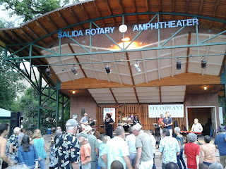 Exterior photo of an amphitheater with performers on stage and people dancing in front of stage.