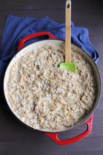 enameled cast iron skillet filled with creamy rice loaded with bean sprouts and ground pork