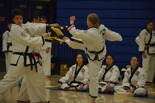 An adult woman black belt breaking a board using martial arts
