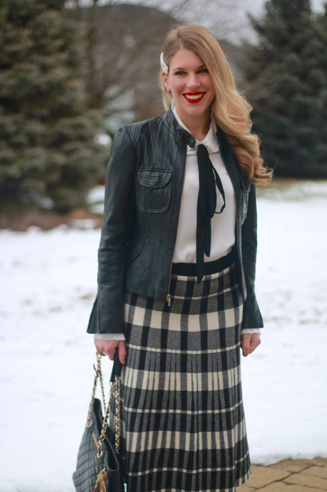 winter work outfit, midi skirt in winter, midi skirt for work, plaid midi skirt, black moto jacket, white bow tie blouse, burgundy boots