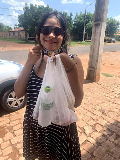 moça jovem de oculos escuros, vestido preto com listras brancas, segurando sacolas de plastico