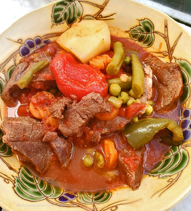 this is a bowl of freshly made beef stew with potatoes, carrots, peas and london broil