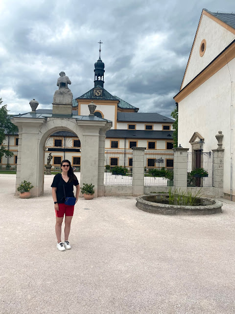 Kat (me) standing in front of white castle and gate in the Czech Republic