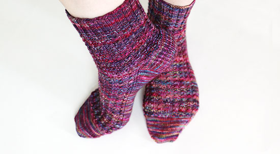 Feet in a casual pose against a white background, wearing hand knit multi-colored socks with a subtle cable rib pattern.