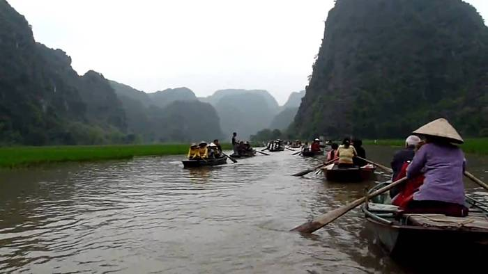 "The Tam Coc (""three caves"") portion is a three-hour excursion by small boat along the Ngô Đồng river,  beginning at the village of Van Lam and proceeding through a scenic landscape dominated by rice fields and karst towers. The route includes floating through three natural caves (Hang Ca, Hang Hai, and Hang Ba), the largest of which is 125m long with its ceiling about 2m high above the water. The boats are typically rowed by one or two local women who also sell embroidered goods."