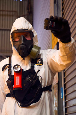 A man in a hazmat suit holds something up to look at it