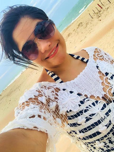 mulher morena, jovem, cabelo preto, oculos escuros, biquini de lstras azuis e brancas em uma praia