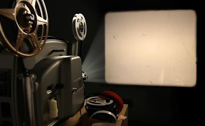 Proyektor film 8mm antik memproyeksikan gambar kosong dengan debu film dan goresan ke dinding di samping tumpukan gulungan film sekarang melalui Getty Images