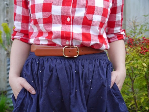 Red and white check shirt, cognac leather belt, navy skirt