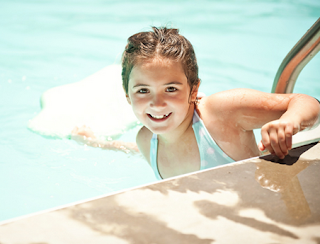 Image of happy girl with a kick board in the pool ready to swim for her children swimming lessons