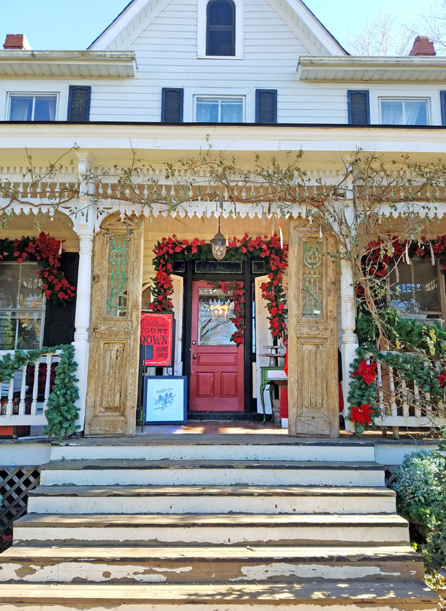 red and vintage Christmas decor in old house porch
