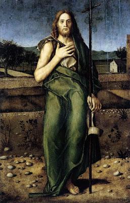 San Juan de pie con una mano en el corazon y en la otra un baston terminado en una cruz