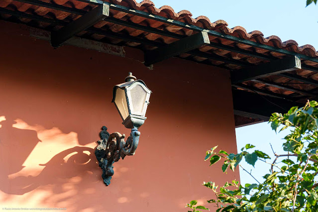 Luminária em estilo antigo, com base em ferro fundido, no canto de uma casa