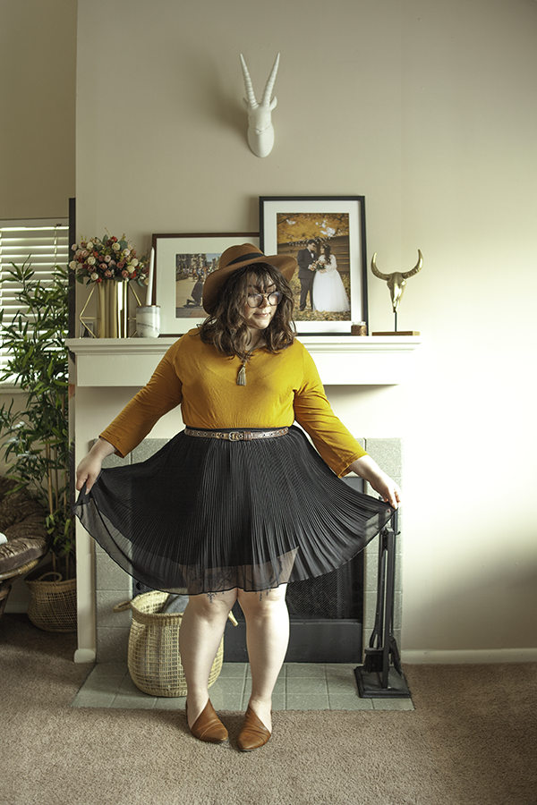 An outfit consisting of a brown panama hat, yellow 3/4 length sleeve top, black pleated mini skirt, and brown d'Orsay flats.