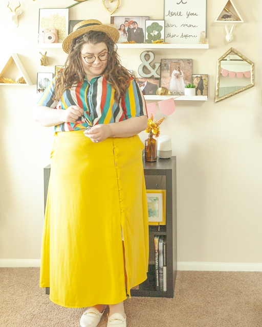 An outfit consisting of a straw boater hat, a light blue, yellow, green, white and black vertical striped collared short sleeve blouse with the ends tied into a bow on top of a yellow button down maxi skirt and white mules.