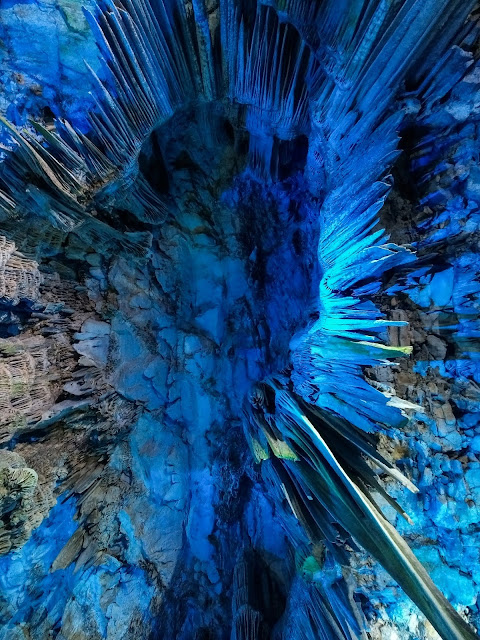 Looking up at the ceiling inside St. Michael's Cave lit up by blue light.