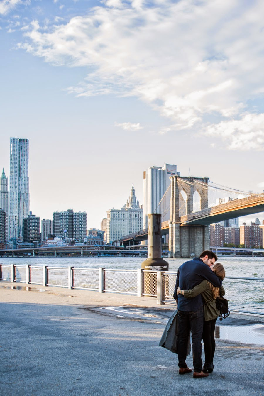 Surprise proposal, kissing under the Brooklyn Bridge NYC - www.cassiecastellaw.com