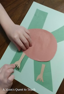 gluing legs of construction paper kiwi onto letter K with glue stick