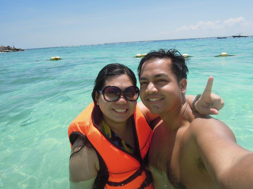Travel couple blogger at the beach of Shangri-La's Mactan Resort and Spa