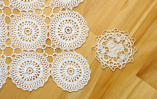 Vintage handmade white cotton crochet doily and coaster on a light wood background.