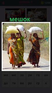 по дороге идут несколько женщин и на головах несут мешки