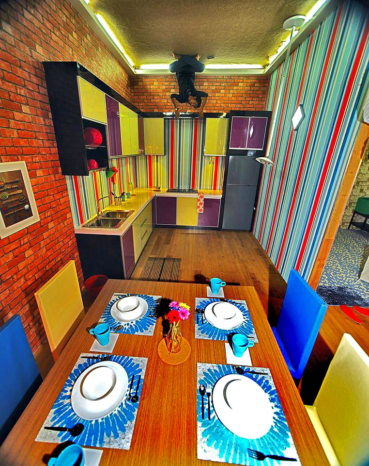 A visitor poses in the dining area of the KL upside down house