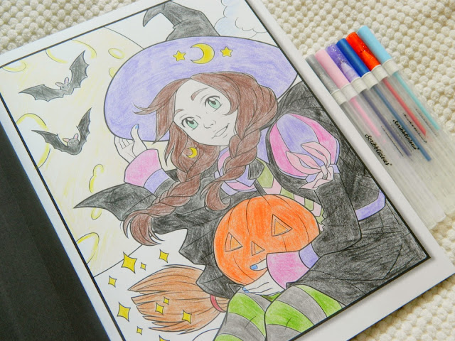 A completed colouring page of a witch holding a jack-o-lantern and some bats in the background