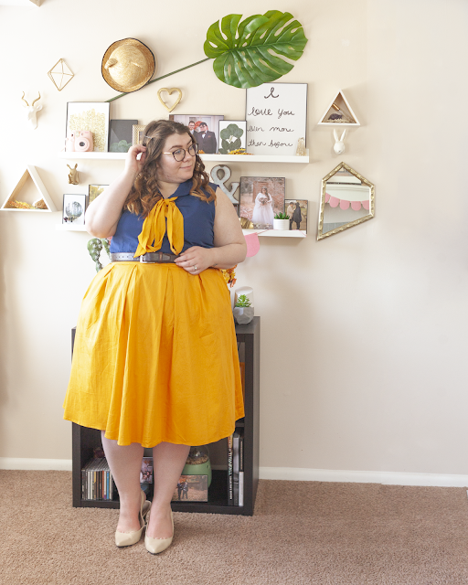 An outfit consisting of a navy blue blouse, a golden yellow ribbon tied in a bow under the collar, tucked into a yellow midi skirt and beige slingback heels.