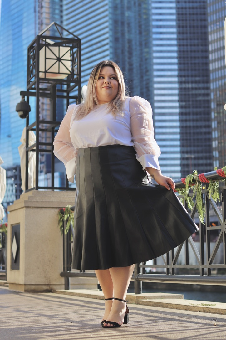 Chicago Plus Size Petite Fashion Blogger, influencer, YouTuber, and model Natalie Craig, of Natalie in the City, reviews Eloquii's faux leather pleated midi skirt and mixed media organza blouse.