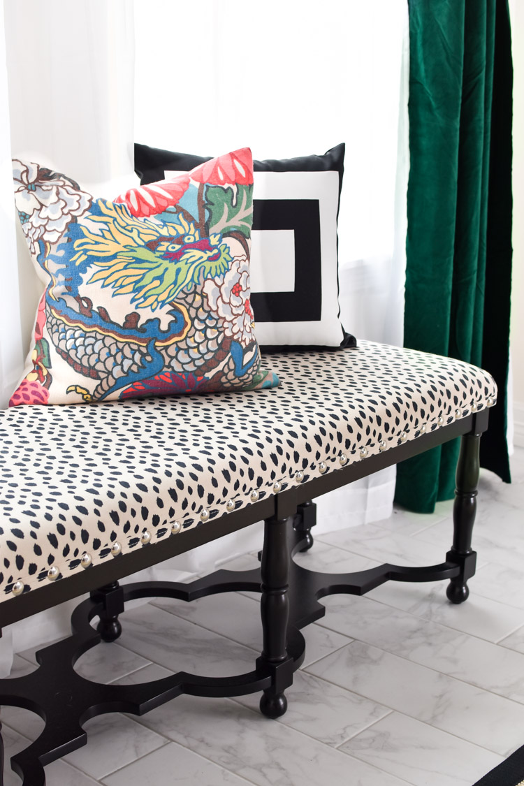 Chiang Mai dragon throw pillow on a black spotted bench in a dining room with green velvet curtains