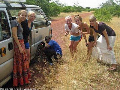 lustige weiße blonde Frauen und schwarzer Mann - Reifen wechseln