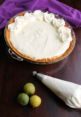 piping cream cheese whipped cream rosettes on top of key lime pie