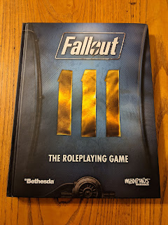 The core rulebook, the cover of which resembles a closeup detail of a section of a uniform from the video game with the insignia that represents the number 111 centred on the cover.