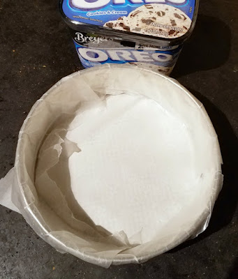 wax paper lined springform pan next to quart of ice cream