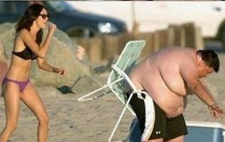 grappige afbeelding dikke man zit vast in de stoel op het strand