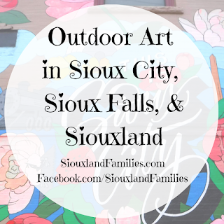 """in background, a floral mural on a wall in Sioux City by Jenna Brownlee. In foreground, the words """"outdoor art in Sioux City, Sioux Falls, & Siouxland"""""""