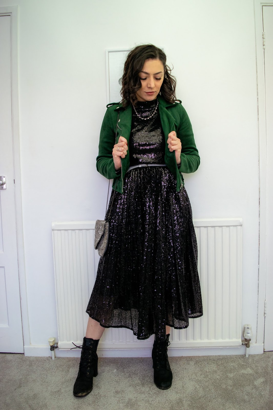 I'm standing and looking down wearing the black sequin pleated dress with a thin twisted silver necklace, a evergreen velvet biker jacket, a embellished silver bag with a silver chain and black heeled Timberland boots.