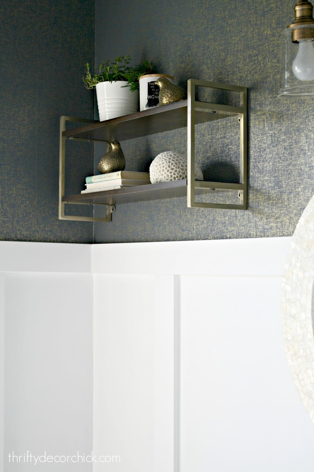 Wood and brass shelves above toilet