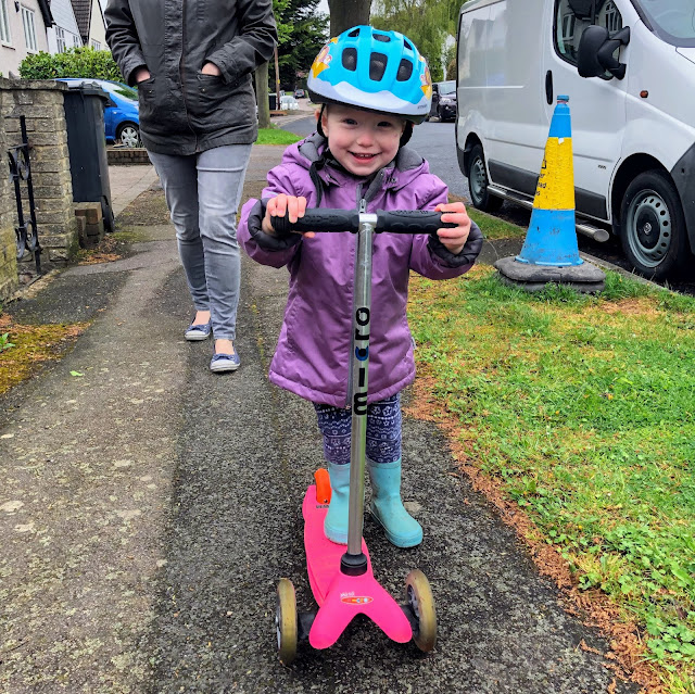 A toddler in a purple coat and blue helmet on a pink microscooter, scooting on a pavement on a residential street