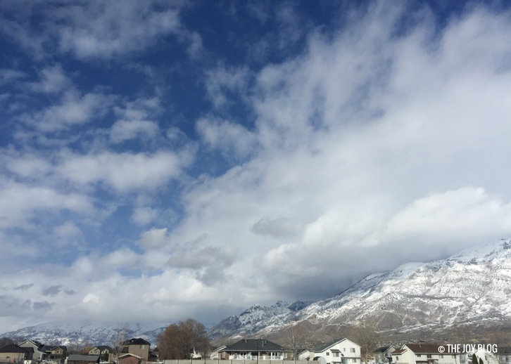 Mountains overlook a city with clouds and snow // www.thejoyblog.net