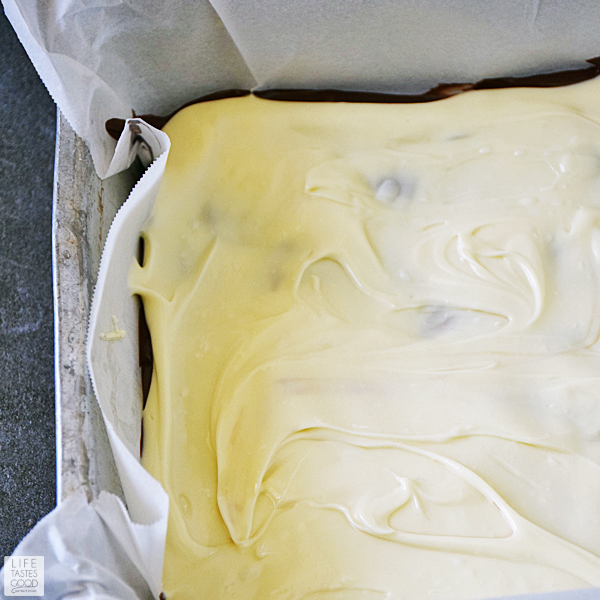 Pour white chocolate over semi-sweet chocolate and spread to cover