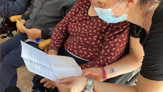 La educadora lee una carta de un alumno a una residente.