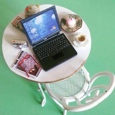 Modern dolls' house miniature table at a cupcake cafe with a laptop, camera, spectacles and magazine on it, plus a cupcake and cup of tea.